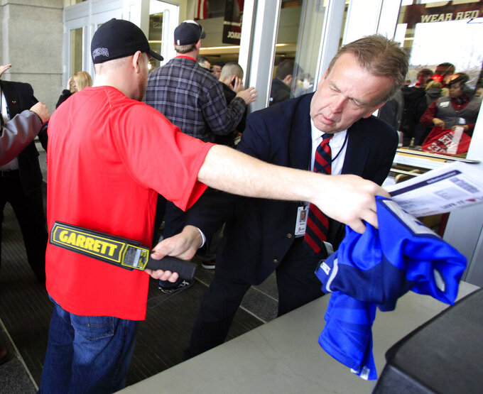 FILE - In this May 2, 2011, file photo, a United Center security officer uses a wand as he checks for prohibited items as a fan arrives for Game 1 of a second-round NBA playoff basketball series between the Chicago Bulls and the Atlanta Hawks, in Chicago. The metal detectors that greet sports fans at the gates might soon be accompanied by thermal body scanners, in the gargantuan task of better protecting venues from virus spread in order to bring the games back for in-person viewing. (AP Photo/Charles Rex Arbogast, File)