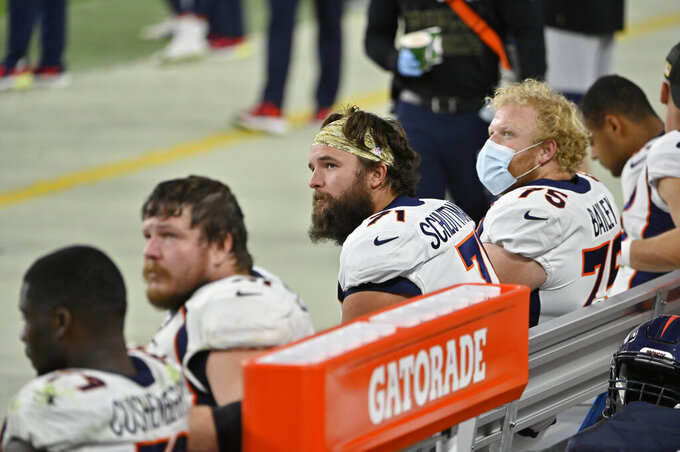 Denver Broncos offensive guard Austin Schlottmann (71) watches from the bench beside teammates as they trail the Las Vegas Raiders during the second half of an NFL football game, Sunday, Nov. 15, 2020, in Las Vegas. (AP Photo/David Becker)