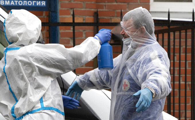 A medical worker wearing gear to protect against coronavirus infection disinfects a driver of his ambulance after escorting a patient to a hospital for COVID-19 patients in St.Petersburg, Russia, Thursday, June 4, 2020. (AP Photo/Dmitri Lovetsky)