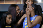 California's Kristine Anigwe, second from left, laughs with UCLA's Kennedy Burke while posing for group photos during NCAA college basketball Pac-12 media day in San Francisco, Wednesday, Oct. 10, 2018. Also pictured are UCLA's Lajahna Drummer, top, and California's Asha Thomas. (AP Photo/Jeff Chiu)