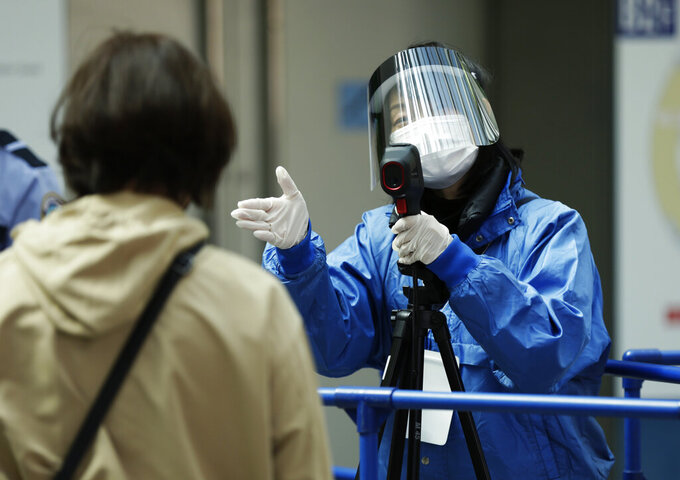 A worker directs a spectator to a next step to enter the arena after taking the person's temperature during the coronavirus pandemic before the ISU World Team Trophy figure skating competition in Osaka, western Japan on April 15, 2021. The picture is still grim in parts of Europe and Asia as variants of the virus fuel an increase in new cases and the worldwide death toll closes in on 3 million. (AP Photo/Hiro Komae, File)