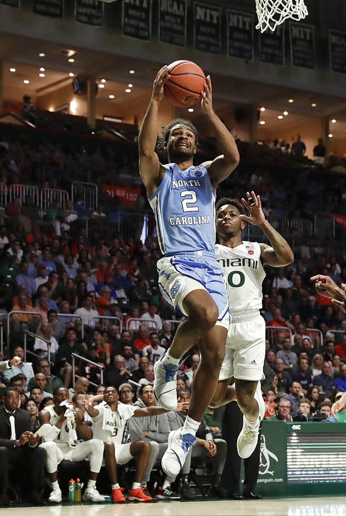 North Carolina guard Coby White shoots and scores against Miami guard Chris Lykes during the first half of an NCAA college basketball game on Saturday, Jan. 19, 2019, in Coral Gables, Fla. (AP Photo/Brynn Anderson)