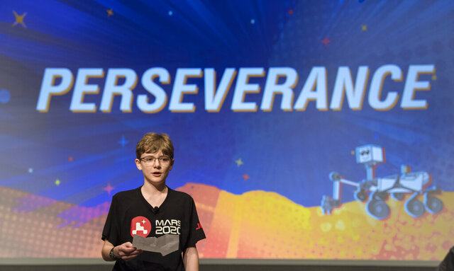 In this image released by NASA, Alex Mather, the student whose submission, Perseverance, was chosen as the official name of the Mars 2020 rover, reads his essay entry, Thursday, March 5, 2020, at Lake Braddock Secondary School in Burke, Va. (Aubrey Gemignani/NASA via AP)