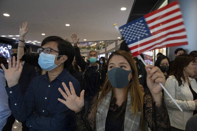 Hongkongers hold up their hands to represent their five demands and a United States flag as they chant