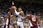 Duke guard Tre Jones (3) drives to the basket while Florida State guard Devin Vassell (24) and forward Malik Osborne (10) defend during the second half of an NCAA college basketball game in Durham, N.C., Monday, Feb. 10, 2020. (AP Photo/Gerry Broome)