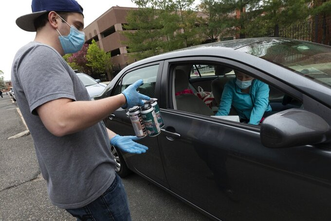 In this Friday, May 8, 2020, photo, Jack's Abby craft brewery employee Casey Mott carries an order to a customer in a line of cars waiting curbside in Framingham, Mass. Sales of wine, spirits and other alcoholic beverages have risen during the coronavirus pandemic. (AP Photo/Michael Dwyer)