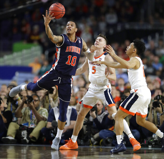 Auburn guard Samir Doughty (10) grabs a loose ball over Virginia guard Kyle Guy, center, and Kihei Clark, right, during the first half in the semifinals of the Final Four NCAA college basketball tournament, Saturday, April 6, 2019, in Minneapolis. (AP Photo/Jeff Roberson)