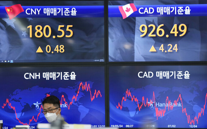 A currency trader walks near the screens showing the foreign exchange rates at the foreign exchange dealing room in Seoul, South Korea, Friday, May 28, 2021. Asian shares rose Friday, powered by encouraging signs that the U.S. economic recovery from the pandemic is gaining momentum. (AP Photo/Lee Jin-man)