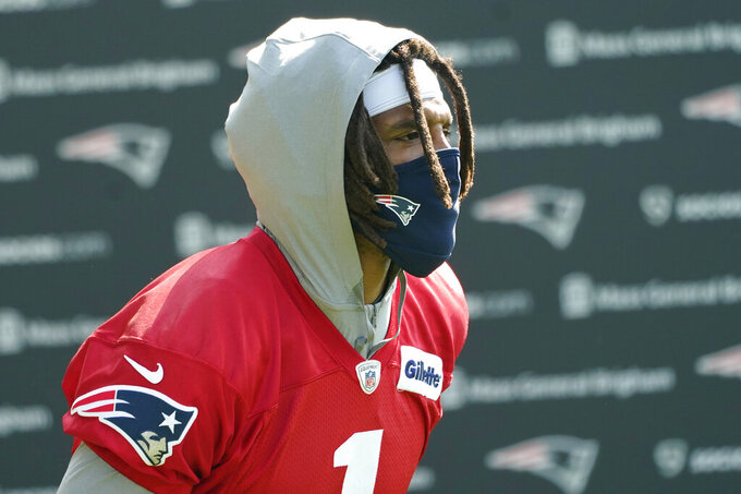 New England Patriots quarterback Cam Newton walks to an NFL football practice, Friday, July 30, 2021, in Foxborough, Mass. (AP Photo/Elise Amendola)