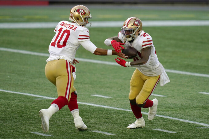 San Francisco 49ers quarterback Jimmy Garoppolo, left, hands off to running back Jeff Wilson Jr., in the first half of an NFL football game against the New England Patriots, Sunday, Oct. 25, 2020, in Foxborough, Mass. (AP Photo/Charles Krupa)