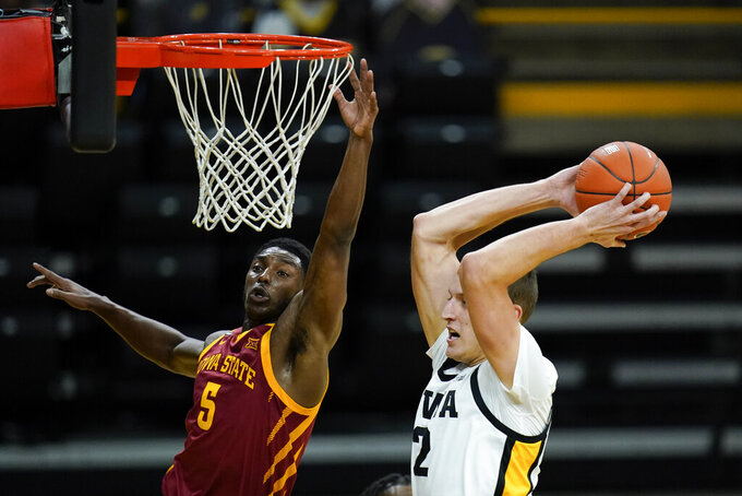 Iowa forward Jack Nunge grabs a rebound in front of Iowa State guard Jalen Coleman-Lands, left, during the first half of an NCAA college basketball game, Friday, Dec. 11, 2020, in Iowa City, Iowa. (AP Photo/Charlie Neibergall)