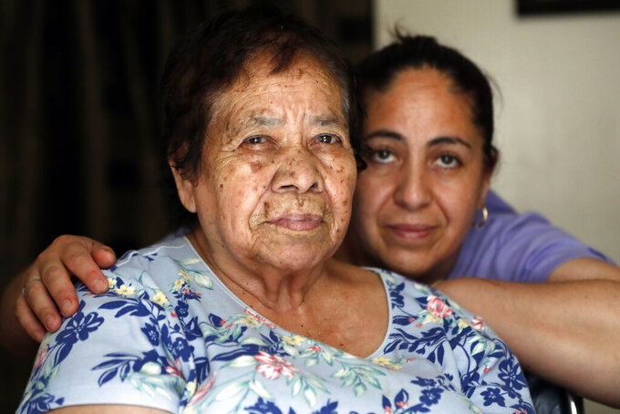Eugenia Rodriguez, right, and her 84-year-old non-citizen mother, Francisca Perez, pose for a portrait in their house Wednesday, June 30, 2021, in Chicago's Little Village neighborhood. Rodriguez hasn't been eligible for insurance coverage after overstaying a visitor visa from Mexico. She used to wake up every two or three hours at night to check on her mother. Since getting health insurance through the Illinois program, her mother has all the medications she needs. (AP Photo/Shafkat Anowar)