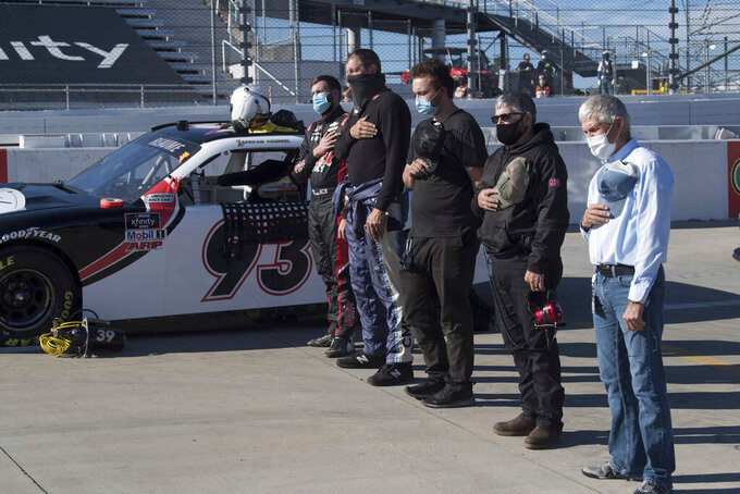 Jeff Green, left, and his crew stand during the national anthem prior to a NASCAR Xfinity Series auto race at Martinsville Speedway in Martinsville, Va., Saturday, Oct. 31, 2020. (AP Photo/Lee Luther Jr.)