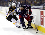 Columbus Blue Jackets forward Cam Atkinson, right, works against Boston Bruins forward David Krejci, of the Czech Republic, during the first period of an NHL hockey game in Columbus, Ohio, Tuesday, March 12, 2019. (AP Photo/Paul Vernon)
