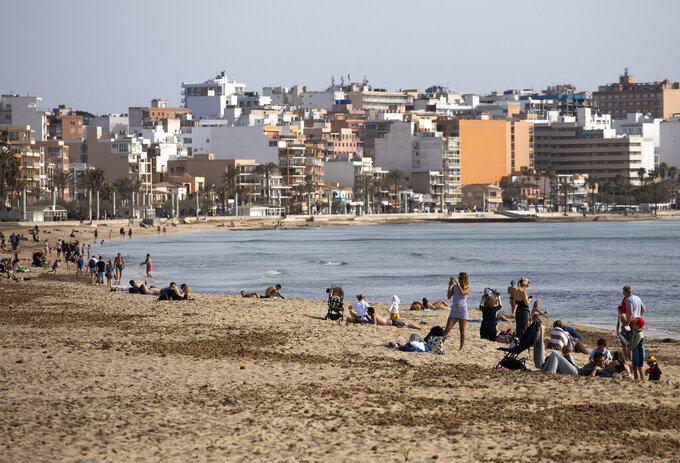 Tourists enjoy the beach at the Spanish Balearic Island of Mallorca, Spain, Monday, March 29, 2021. Efforts in Spain to restart tourism activity is drawing a mixed picture due to a patchwork of national, regional and European rules on travel that is confusing both tourists and their hosts. (AP Photo/Francisco Ubilla)