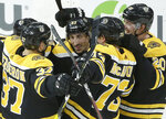 Boston Bruins' Brad Marchand, center, celebrates after scoring the winning goal in overtime with teammates Patrice Bergeron (37), Charlie McAvoy (73) and Joakim Nordstrom (20), of Sweden, against the Colorado Avalanche in an NHL hockey game, Sunday, Feb. 10, 2019, in Boston. (AP Photo/Steven Senne)