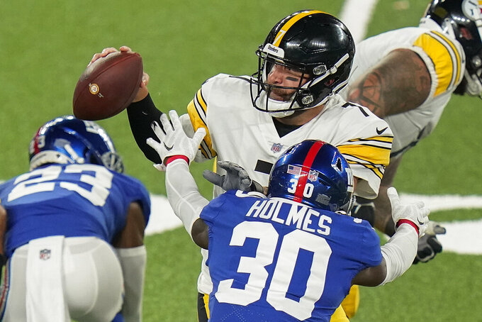 Pittsburgh Steelers quarterback Ben Roethlisberger (7) looks to pass under pressure from New York Giants cornerback Darnay Holmes (30) during the first quarter of an NFL football game Monday, Sept. 14, 2020, in East Rutherford, N.J. (AP Photo/Frank Franklin II)