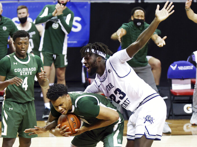 Colorado State forward Dischon Thomas (11) holds the ball as Utah State center Neemias Queta (23) reaches for it during the first half of an NCAA college basketball game in the semifinals of the Mountain West Conference men's tournament Friday, March 12, 2021, in Las Vegas. (AP Photo/Isaac Brekken)