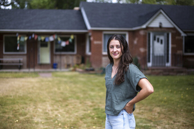 Sara Dery, who was born in Jackson, Wyo., and raised in Victor, Idaho, stands in the front yard of her rental home Monday, Aug. 2, 2021, in Jackson, Wyo. Dery recently found out that her rental home and the home and commercial building on the adjacent lots near East Kelly Kelly Avenue and Vine Street are being sold for $14 million. (Ryan Dorgan/Jackson Hole News & Guide via AP)