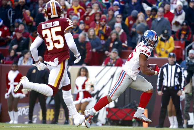 New York Giants running back Saquon Barkley, right, looks at Washington Redskins free safety Montae Nicholson (35) while scoring on a touchdown pass from quarterback Daniel Jones during the first half of an NFL football game, Sunday, Dec. 22, 2019, in Landover, Md. (AP Photo/Alex Brandon)