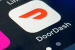 FILE - This Feb. 27, 2020 shows the DoorDash app on a smartphone in New York. DoorDash is suing New York City over a new law that requires delivery companies to share customer data with restaurants. The lawsuit, filed Wednesday, Sept. 15, 2021 is the latest in a string of legal tussles between the delivery companies and local governments, reflecting unease over the phenomenal growth of delivery and its impact on restaurants. (AP Photo, File)