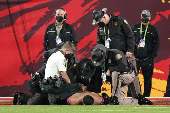 Police detain a fan who ran on the field during the second half of the NFL Super Bowl 55 football game between the Tampa Bay Buccaneers and the Kansas City Chiefs, Sunday, Feb. 7, 2021, in Tampa, Fla. (AP Photo/David J. Phillip)
