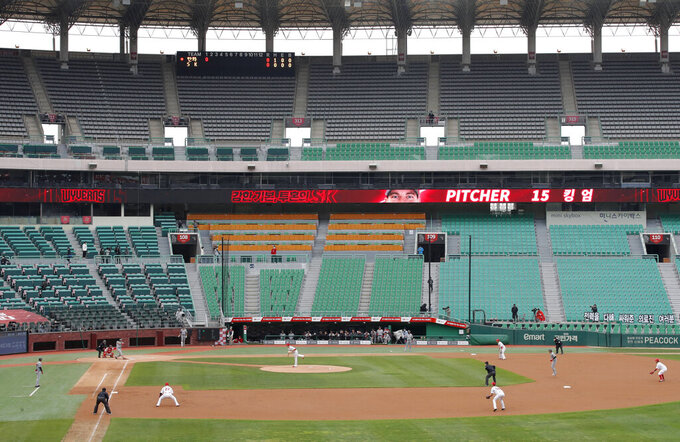 Stadium seats are empty as a part of precaution against the new coronavirus during a baseball game between Hanwha Eagles and SK Wyverns in Incheon, South Korea, Tuesday, May 5, 2020. With umpires fitted with masks and cheerleaders dancing beneath vast rows of empty seats, a new baseball season got underway in South Korea following a weeks-long delay because of the coronavirus pandemic. (AP Photo/Lee Jin-man)