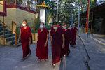 Exile Tibetan Buddhist monks wear masks as protection against the coronavirus as they circumambulate the residence of Tibetan spiritual leader the Dalai Lama in Dharmsala, India, Sunday, Sept. 27, 2020. (AP Photo/Ashwini Bhatia)