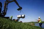 In this Wednesday, April 24, 2019 photo, Kamailelani Napoleon, with Environmental Restoration, works with Bruce Amsden to remove an orphaned LP tank from the side of levee on W, outside of Pacific Junction, Iowa.  The Environmental Protection Agency has been trying to find, organize, return or dispose of containers holding hazardous materials that were carried away by the flood waters. (Brian Powers/The Des Moines Register via AP)