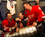 """FILE - In this June 16, 1998 file photo, Vladimir Konstantinov, center, holds the Stanley Cup in his lap and pours champagne for defenseman Viacheslav Fetisov, left, as center Igor Larionov looks on in a post game locker room celebration after beating the Washington Capitals 4-1 in Game 4 to take the Stanley Cup at the MCI Center in Washington.  More than two decades since Fetisov and the """"Russian Five"""" shattered the myth that NHL teams couldn't win with players from a nation unpopular in North America, the St. Louis Blues' Russian Two of Vladimir Tarasenko and Ivan Barbashev are one victory away from lifting the same Cup after being inspired by the generation of countrymen who endured so much to get there. (AP Photo/Wilfredo Lee, File)"""
