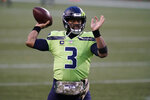 Seattle Seahawks quarterback Russell Wilson passes during warmups before an NFL football game against the Arizona Cardinals, Thursday, Nov. 19, 2020, in Seattle. Wilson's hand-warmer is part of the NFL's