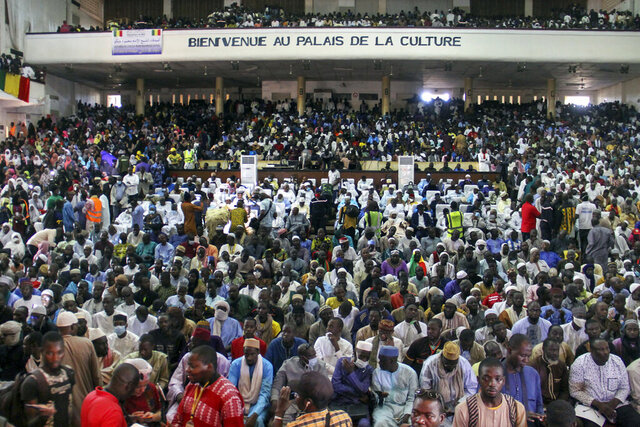 People attend a prayer service led by Mahmoud Dicko, an imam who helped lead the opposition protests, for those who died or were injured during the protests, in Bamako, Mali Friday, Aug. 28, 2020. West African leaders on Friday urged Mali's junta to take no more than one year to hand over power to a civilian government, as regional heads of state held another virtual summit after initial negotiations with the military coup leaders failed. (AP Photo/Arouna Sissoko)