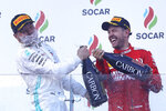 Mercedes driver Valtteri Bottas of Finland, left, celebrates with third placed Ferrari driver Sebastian Vettel of Germany after winning the Formula One Grand Prix at the Baku Formula One city circuit in Baku, Azerbaijan, Sunday, April 28, 2019. (AP Photo/Sergei Grits)