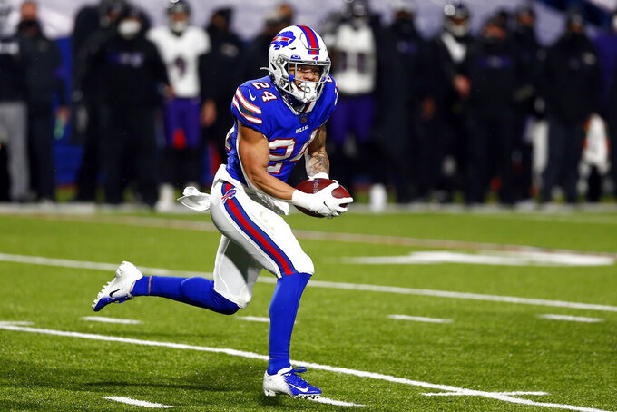 Buffalo Bills cornerback Taron Johnson (24) runs back an interception for a touchdown during the second half of an NFL divisional round football game against the Baltimore Ravens Saturday, Jan. 16, 2021, in Orchard Park, N.Y. (AP Photo/John Munson)