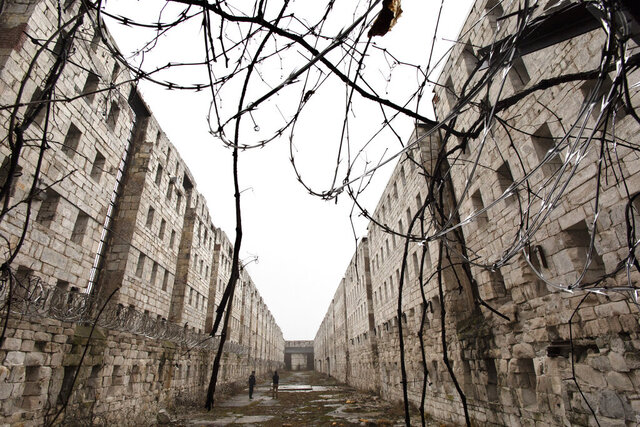 In this Feb. 13, 2020 photo, concertina wire and vines line the stone walls of a former cell block at Sing Sing Correctional Facility in Ossining, N.Y. The hollowed-out building used to house cells for 1,200 men on six tiers and runs well longer than a football field. A not-for-profit group is planning to open the Sing Sing Prison Museum in 2025. Their mission will be to provide a historical picture of incarceration in America while telling the story of one of the county's most well-known prisons. (AP Photo/Mark Lennihan)