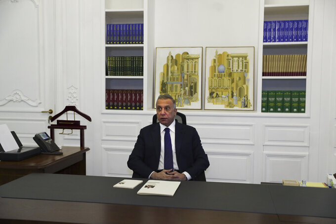 Iraqi Prime Minister Mustafa al-Kadhimi poses in his office during an interview with The Associated Press in Baghdad, Iraq, Friday, July 23, 2021. (AP Photo/Khalid Mohammed)