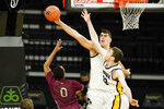 Iowa center Luka Garza, center, and forward Patrick McCaffery block a shot by North Carolina Central guard Jamir Moultrie (0) during the first half of an NCAA college basketball game, Wednesday, Nov. 25, 2020, in Iowa City, Iowa. (AP Photo/Charlie Neibergall)