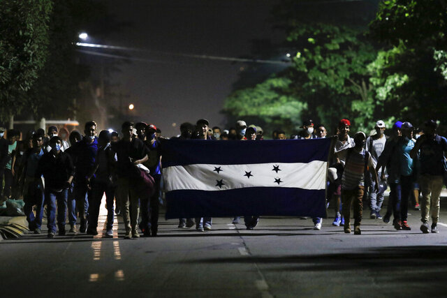 Honduran migrants trying to reach the U.S. border walk along a highway carrying their national flag as they leave San Pedro Sula, Honduras, before dawn Friday, Jan. 15, 2021. The group quickly dispersed along the heavily-trafficked highway to the border town of Agua Caliente, but estimates of their number ranged from 2,000 to more than twice that. (AP Photo/Delmer Martinez)