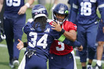Seattle Seahawks quarterback Russell Wilson, right, hugs running back Josh Johnson at the start of NFL football practice Tuesday, June 8, 2021, in Renton, Wash. (AP Photo/Ted S. Warren)