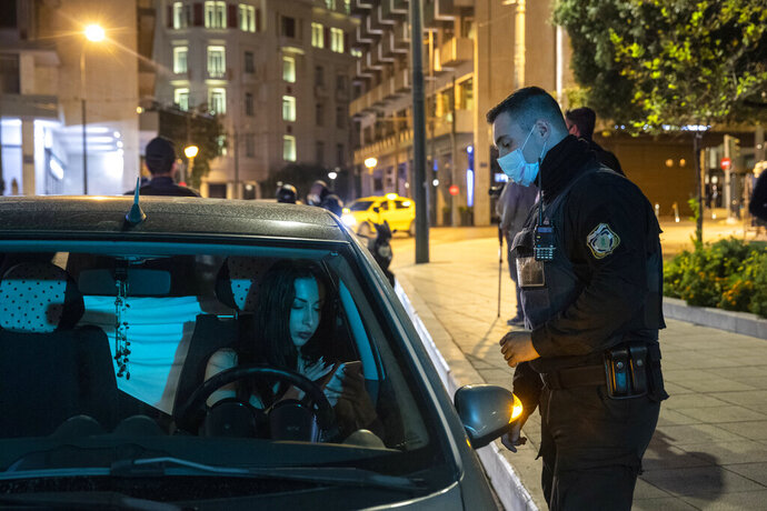 A policeman checks documents of a driver at central Syntagma square in Athens, Greece, Sunday, Oct. 25, 2020. Greece's government has imposed a nightly curfew in greater Athens and other areas with high infection rates as well as a mask requirement. (AP Photo/Yorgos Karahalis)