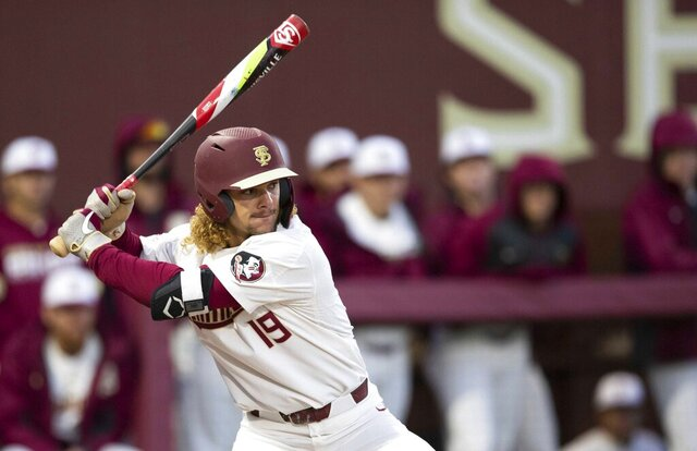 Florida State NCAA college baseball outfielder Elijah Cabell (19) bats against the Univ. of Cincinnati, Friday, Feb. 21, 2020, in Tallahassee, Fla. If all had gone as he hoped, Cabell and his Florida State teammates would be playing for the College World Series championship this week. Instead, Cabell treks to a ball field in his neighborhood in Winter Park, Florida, most days to work on his game in solitude.  (Alicia Devine/Tallahassee Democrat via AP)
