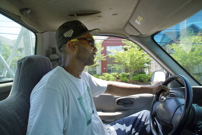 """Alton Lucas drives home after dropping some firewood at a local convenience store outside of Raleigh, N.C., on Friday, June 18, 2021. """"I started the landscaping company, to be honest with you, because nobody would hire me because I have a felony,"""" said Lucas, whose business got off the ground with the help of Inmates to Entrepreneurs, a national nonprofit assisting people with criminal backgrounds by providing practical entrepreneurship education. (AP Photo/Allen G. Breed)"""