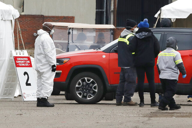 Health care officials watch as a vehicle approaches a testing site at the Michigan State Fairgrounds, Friday, March 27, 2020, in Detroit. The city set up several stations at the fairgrounds to allow for drive up testing for the coronavirus. (AP Photo/Carlos Osorio)