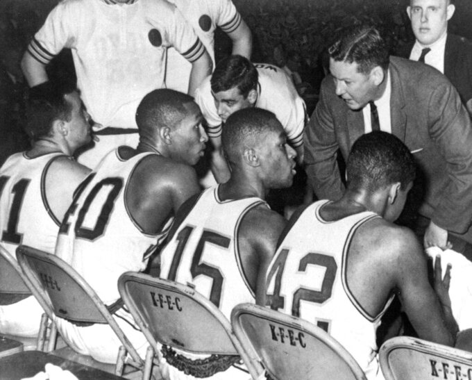 FILE - In this March 23, 1963, file photo, Loyola coach George Ireland, right, bends over to issue orders to his team that was trailing Cincinnati in the final game of the National Collegiate basketball championship at Louisville, Ky. Players, from left to right, are: John Egan, Vic Rouse, Jerry Harkness and Ron Miller. Loyola Chicago guard Lucas Williamson is lending his voice and perspective to an upcoming documentary. The film is about the Ramblers' barrier-breaking team that won the 1963 NCAA championship. (AP Photo/File)