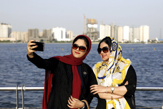 In this Saturday, July 7, 2019, photo, Iranians take selfie around of the Persian Gulf Martyrs lake, west of Tehran, Iran.  A few daring women in Iran's capital have been taking off their mandatory headscarves, or hijabs, in public, risking arrest and drawing the ire of hard-liners. Many others stop short of outright defiance and opt for loosely draped scarves that show as much hair as they cover. More women are pushing back against the dress code imposed after the 1979 Islamic Revolution, and activists say rebelling against the hijab is the most visible form of anti-government protest in Iran today. (AP Photo/Ebrahim Noroozi)