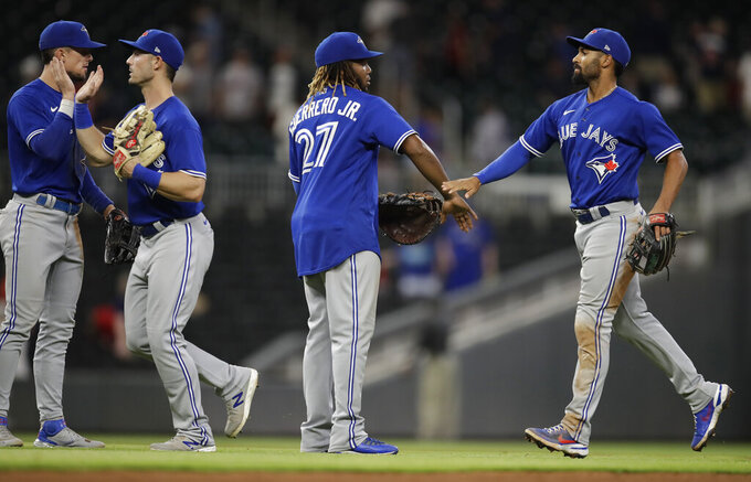 Toronto Blue Jays including Vladimir Guerrero Jr. (27) celebrates at the end of a baseball game against the Atlanta Braves Tuesday, May 11, 2021, in Atlanta. (AP Photo/Ben Margot)