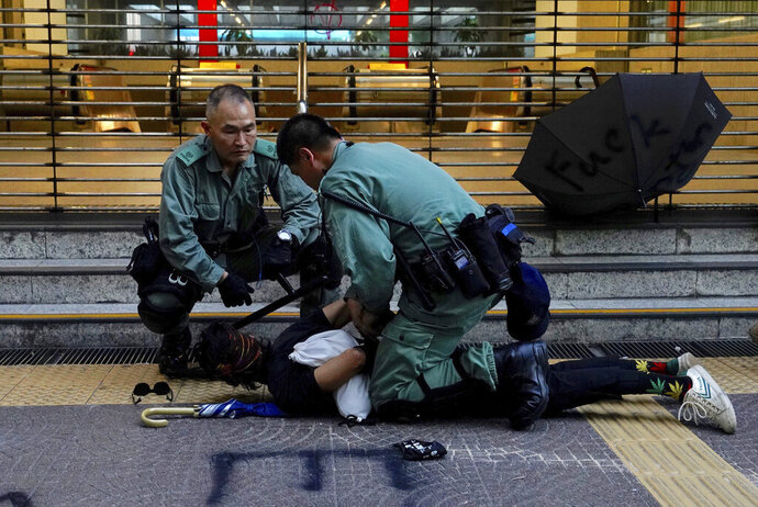 Hong Kong police detain a protester on the streets of Hong Kong on Saturday, Oct. 5, 2019. All subway and train services were suspended, lines formed at the cash machines of shuttered banks, and shops were closed as Hong Kong dusted itself off and then started marching again Saturday after another night of rampaging violence decried as