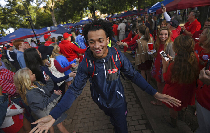 FILE - In this Nov. 5, 2016, file photo, Mississippi tight end Evan Engram greets fans during the Walk of Champions in the Grove before an NCAA college football game between Mississippi and Georgia Southern in Oxford, Miss. When the virus wanes enough to allow the games to begin again, the very essence of these events will likely be missing. (AP Photo/Thomas Graning, File)