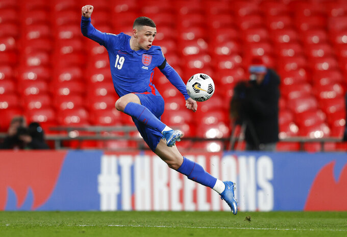 FILE - In this Thursday March 25, 2021 file photo, England's Phil Foden attempts to control the ball during the World Cup 2022 group I qualifying soccer match between England and San Marino at Wembley stadium in London. Exciting talents like Phil Foden, Joao Felix and Ferran Torres are among a host of young players set to play their first major international tournaments at Euro 2020. UEFA has expanded squads from 23 players to 26 and that could encourage coaches to take a chance on more up-and-comers.(Adrian Dennis/Pool Photo via AP, File)
