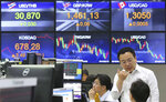 A currency trader gestures at the foreign exchange dealing room of the KEB Hana Bank headquarters in Seoul, South Korea, Tuesday, July 16, 2019. Asian shares were little changed and mixed in quiet trading Tuesday amid a lack of fresh market-moving news as investors looked ahead to earnings season. (AP Photo/Ahn Young-joon)